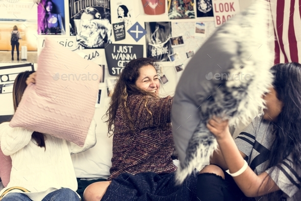 Teenage girls in a bedroom having a pillow fight slumber party and childhood concept - Stock Photo - Images