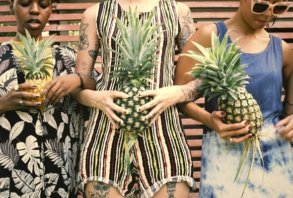 Group of diverse women standing holding pineapple together - Stock Photo - Images