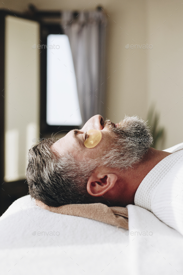 Man relaxing with a golden eye mask treatment - Stock Photo - Images