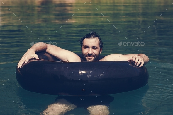 Happy man floating around in the water - Stock Photo - Images