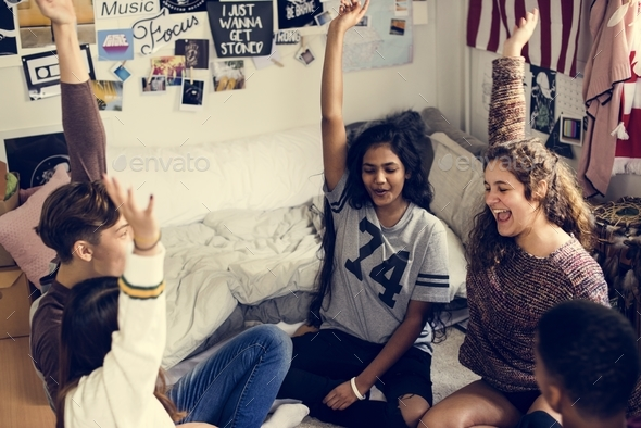 Group of teenagers in a bedroom arms raised community and temwork concept - Stock Photo - Images