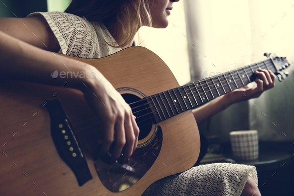 Girl playing an acoustic guitar - Stock Photo - Images
