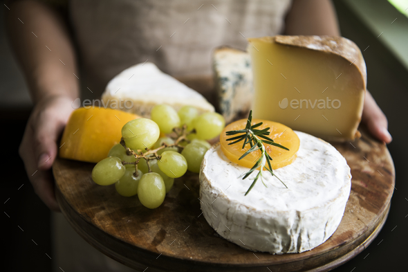 Variation of cheese and green grapes on a wooden platter food photography recipe idea - Stock Photo - Images