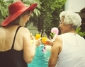 Senior couple women with orange juice by the pool together - PhotoDune Item for Sale