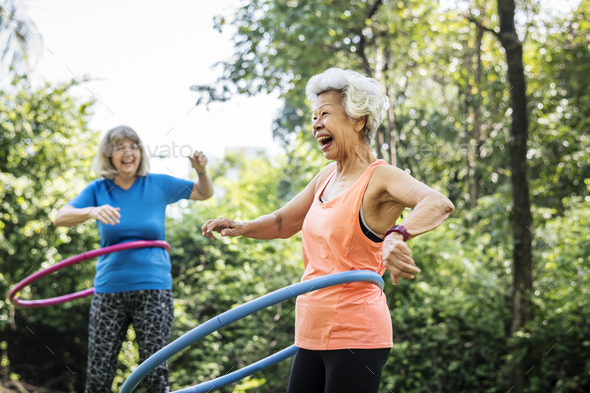 Senior woman exercising with a hula hoop - Stock Photo - Images