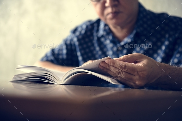 Senior man reading book at home - Stock Photo - Images