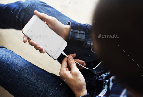 Woman using and charging a smartphone copy space - Stock Photo - Images