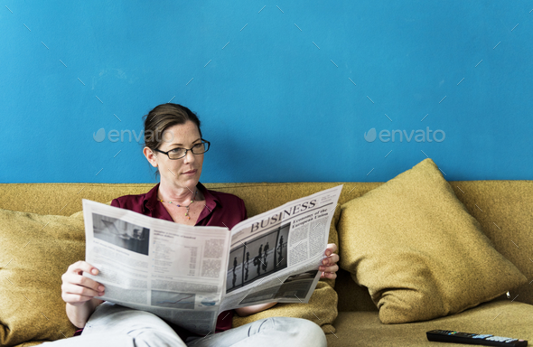 Caucasian woman reading the newspaper - Stock Photo - Images