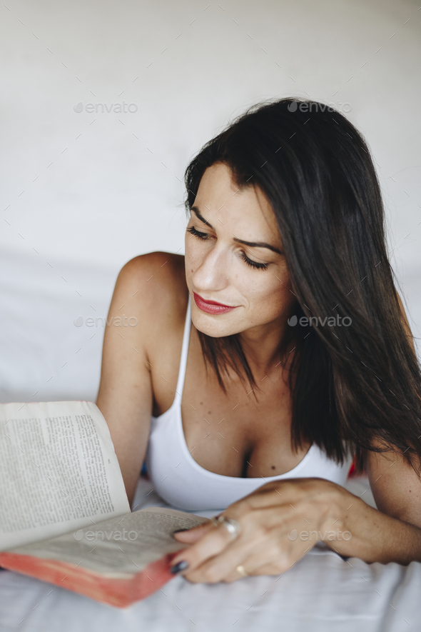 Woman reading a book in bed - Stock Photo - Images