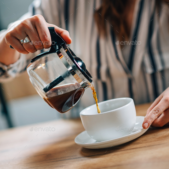 Pouring coffee from kettle - Stock Photo - Images