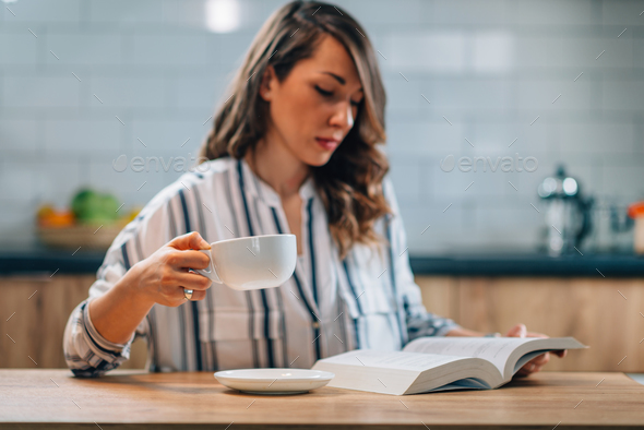 Woman drinking coffee and reading book - Stock Photo - Images