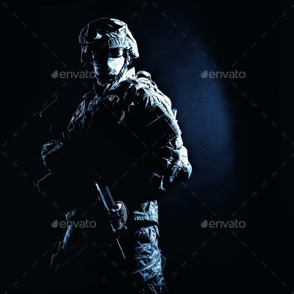 Infantry rifleman standing with weapon in darkness - Stock Photo - Images