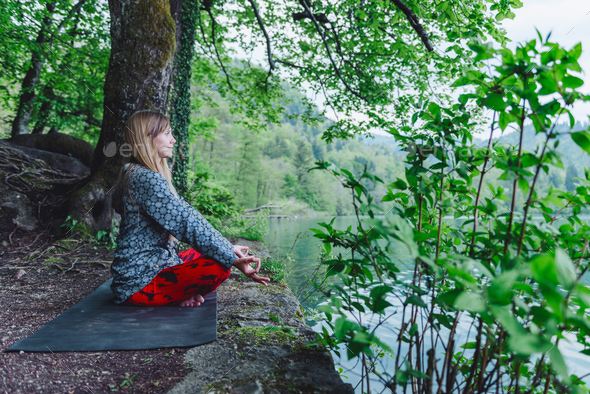 Meditating by the lake - Stock Photo - Images
