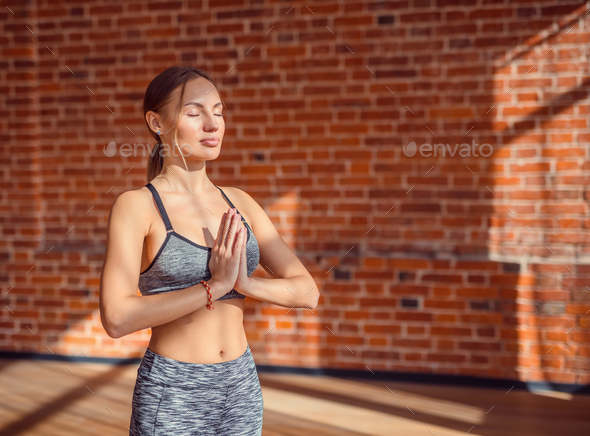 Attractive instructor meditating in the loft - Stock Photo - Images
