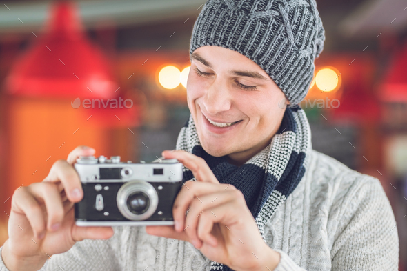Smiling man with a retro camera - Stock Photo - Images