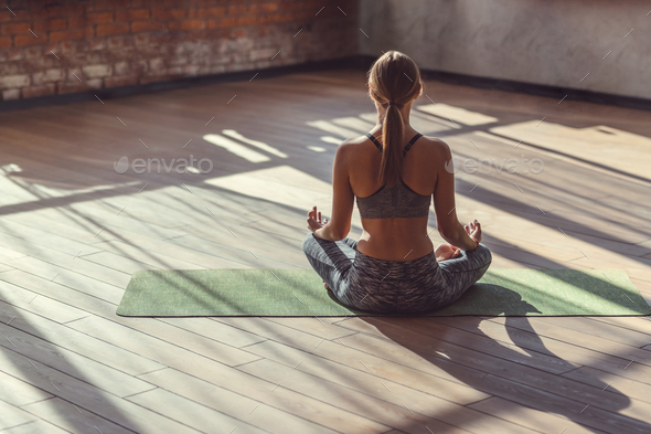 Young woman in lotus pose indoors - Stock Photo - Images