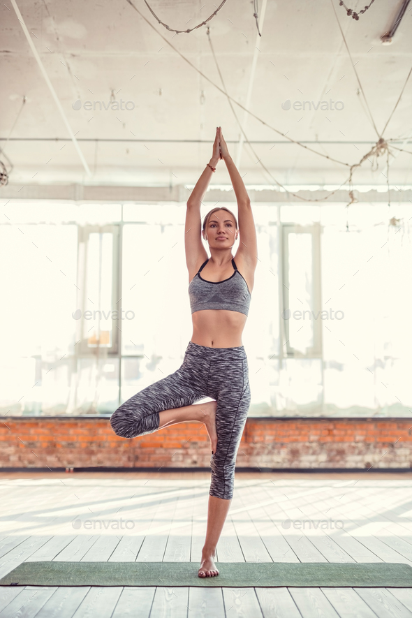 Young instructor practicing yoga in a yoga class - Stock Photo - Images