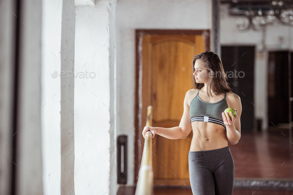Attractive young girl with a green apple - Stock Photo - Images