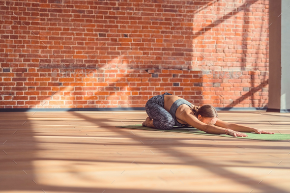 Young instructor doing yoga in the loft - Stock Photo - Images