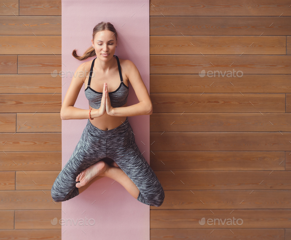 Young girl meditating in yoga class - Stock Photo - Images