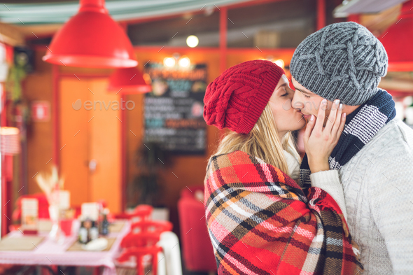 Kissing young couple in cafe - Stock Photo - Images