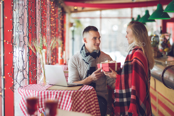 Smiling couple with a gift on a date - Stock Photo - Images