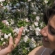 Young Caucasian Woman Sniffs Flowers of Blooming Apple Trees in Garden - VideoHive Item for Sale