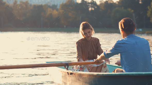 Young couple in a boat at sunset - Stock Photo - Images