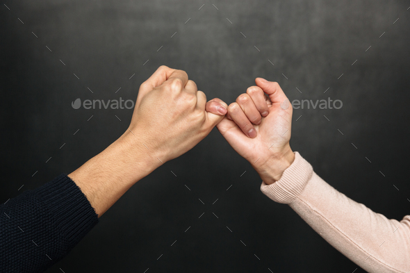 Cropped image of Asian couple holding pinkies to each other - Stock Photo - Images