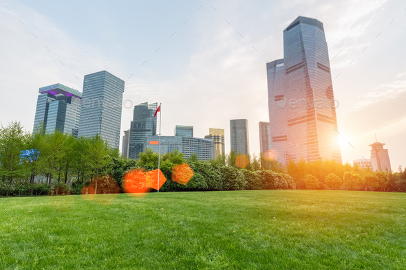 city park lawn with modern building in sunset - Stock Photo - Images