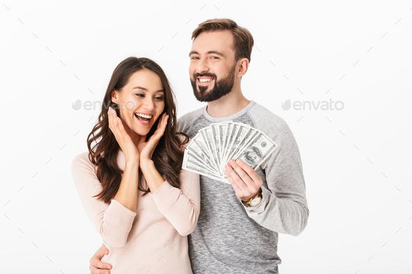 Happy young loving couple holding money. - Stock Photo - Images