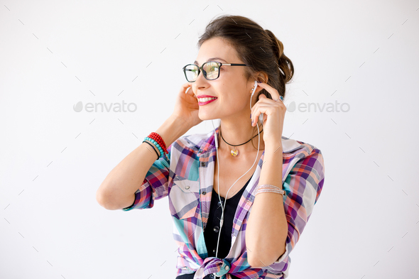 Lovely young woman looking to right enjoy music - Stock Photo - Images