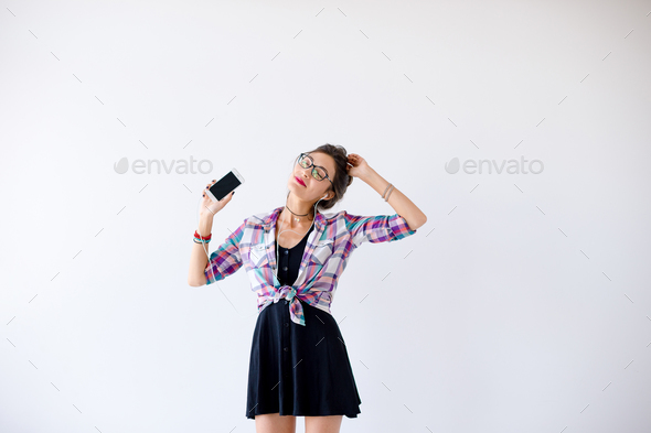 Girl in headphones and glasses listening to music and dancing - Stock Photo - Images