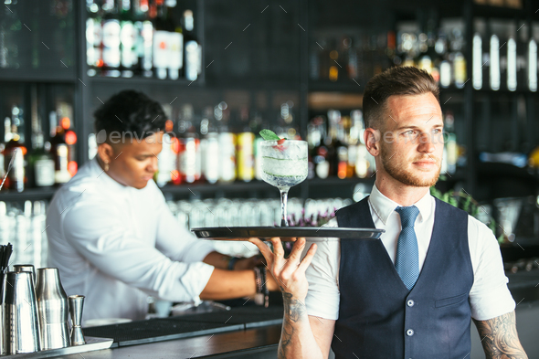 Elegant waiter serving a cocktail - Stock Photo - Images