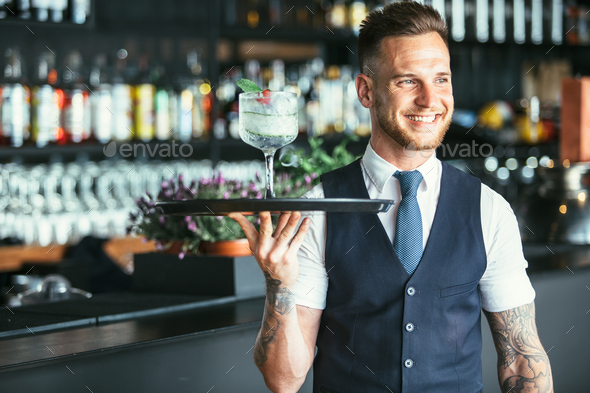 Smiling waiter ready to serve a cocktail - Stock Photo - Images