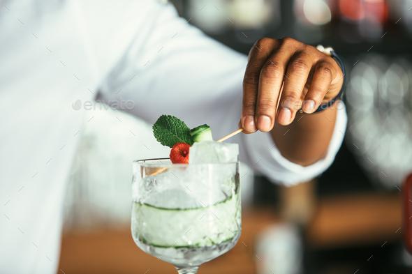 Bartender hands decorating cocktail - Stock Photo - Images