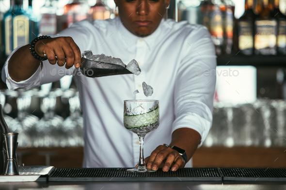 Bartender adding ice - Stock Photo - Images