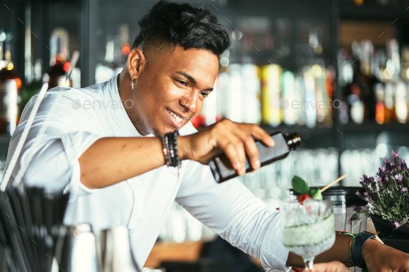 Smiling bartender serving cocktail - Stock Photo - Images