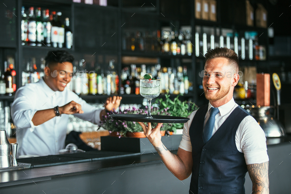 Smiling waiter with a cocktail - Stock Photo - Images