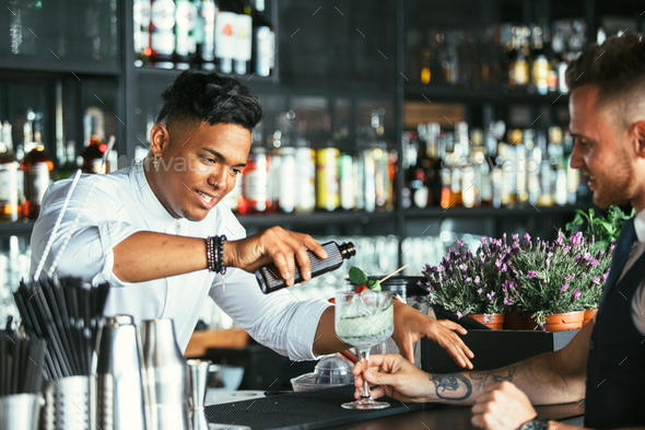 Bartender prepares a cocktail to a waiter - Stock Photo - Images