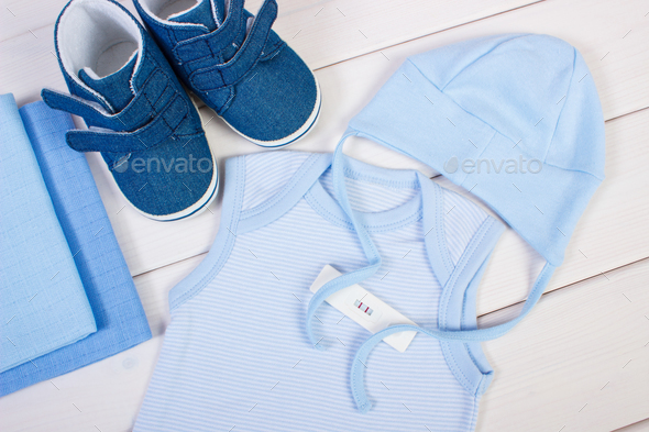 Pregnancy test with positive result and clothing for newborn, expecting for baby concept - Stock Photo - Images