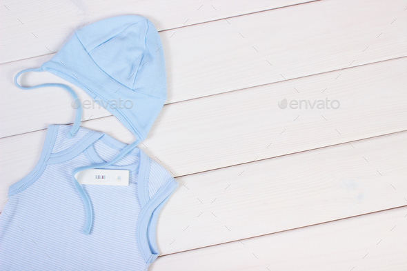 Pregnancy test with positive result and clothing for newborn, copy space for text - Stock Photo - Images