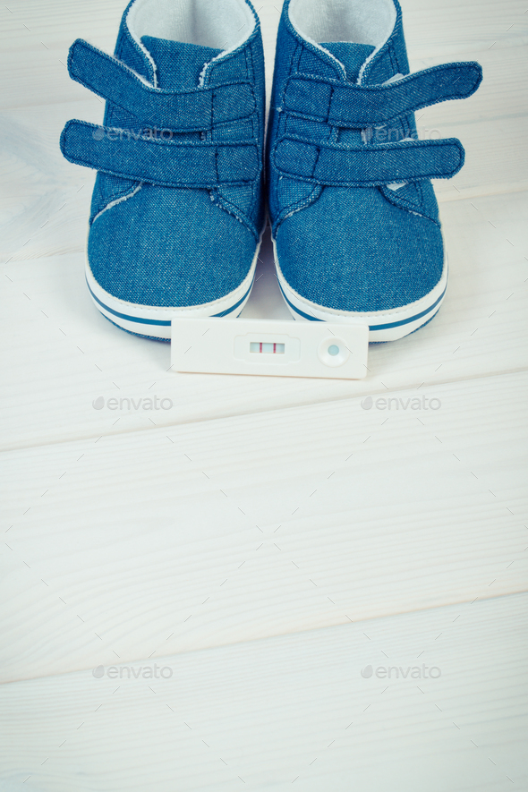 Pregnancy test with positive result and baby shoes for newborn - Stock Photo - Images