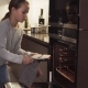 Girl Puts Cookies in Oven for Baking in Modern Kitchen at Home - VideoHive Item for Sale