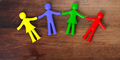 Colorful human figures holding hands laying on wooden background. 3d illustration