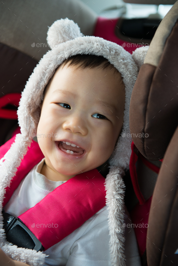 Portrait of cute toddler boy sitting in car seat. - Stock Photo - Images