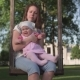 Mother with Baby Swinging on Wooden Swing in Green Park Outside - VideoHive Item for Sale