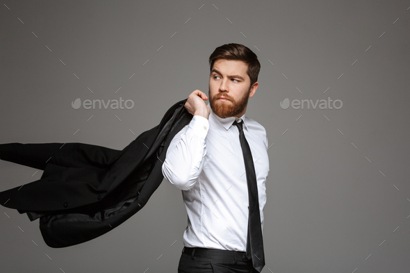 Portrait of a confident young businessman posing with jacket - Stock Photo - Images