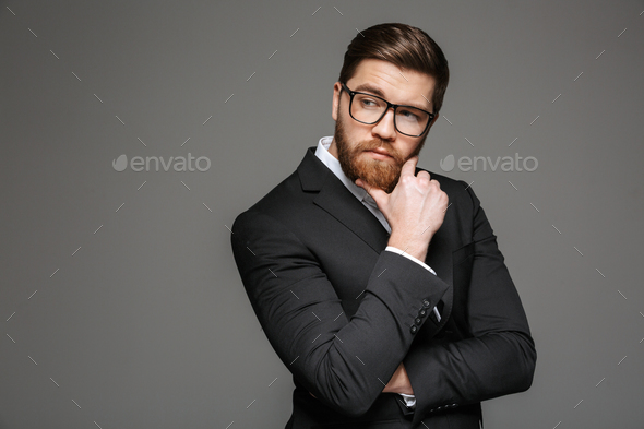 Portrait of a pensive young businessman - Stock Photo - Images