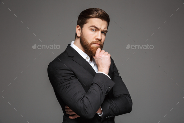Portrait of a pensive young businessman dressed in suit - Stock Photo - Images